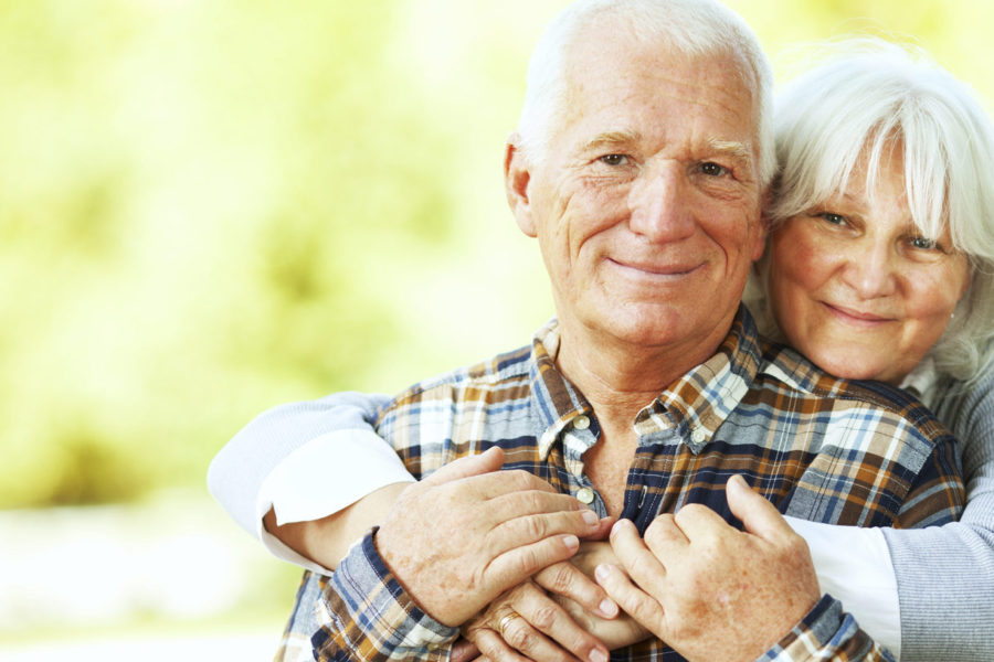 Picture of a smiling senior woman standing behind a senior man with her arms around him. They are both smiling and looking in to the camera. In the blurred background is green park with trees and a walking path.