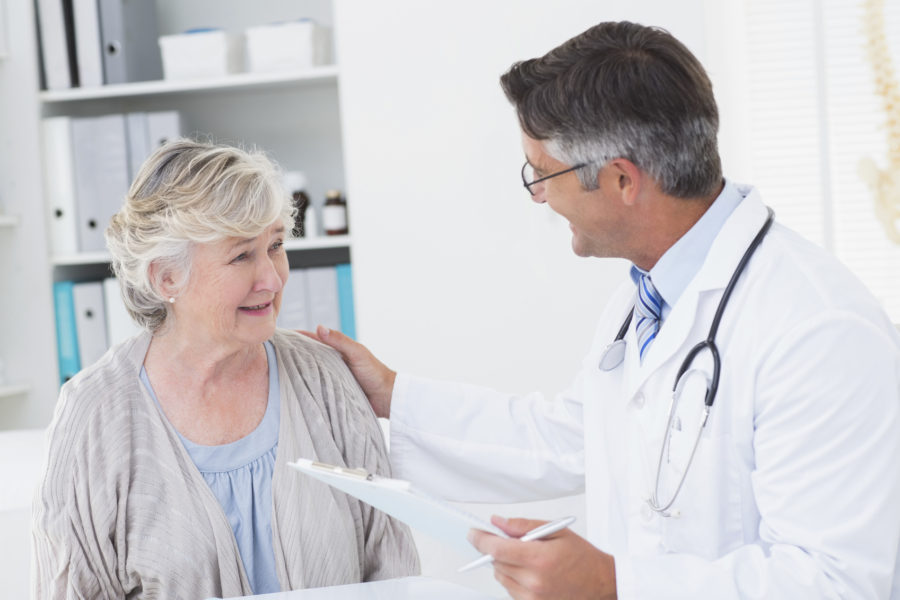 Male doctor consoling senior woman in clinic